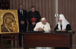 "Pope Francis, sitting left, and Russian Orthodox Patriarch Kirill speak during the signing of a joint declaration on religious unity in Havana, Cuba, Friday, Feb. 12, 2016. The two religious leaders met for the first-ever papal meeting, a historic development in the 1,000-year schism within Christianity. "" (Ismael Francisco/Cubadebate via AP)"